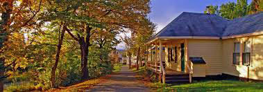Photograph of Quimby Country with a cottage on the right and autumn trees on the left.
