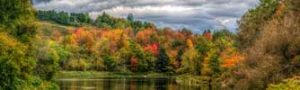 A scene of country Vermont showing autumn trees around a lake